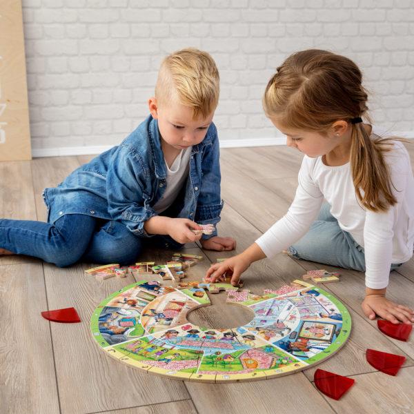 2 Kinder im Kindergartenalter sitzen am Boden und um das runde XXL Lernpuzzle von beleduc