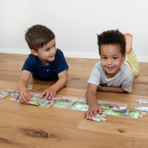 2 Kinder im Kindergartenalter liegen am Boden und haben Spaß beim Zusammensetzen des Dino Puzzles