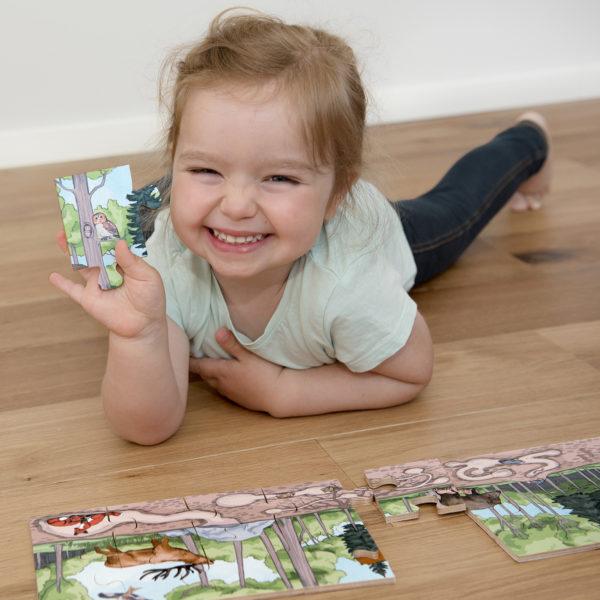 Mädchen im Kindergartenalter liegt am Boden und setzt das Puzzle Entdecke den Wald zusammen