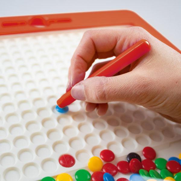 Detailansicht des Magnetspiels Kunterbunt. Mit dem Magnetstift wird eines der bunten Steinchen aufgehoben und im Raster abgelegt