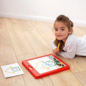 Mädchen im Kindergartenalter liegt am Boden und zeichnet mit dem Magnetstift des Magnetspiels Kunterbunt eine Vorlagenkarte nach