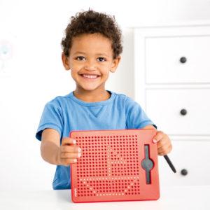 Bub im Kindergartenalter zeigt sein, auf der Magnetzeichentafel gemaltes Bild