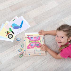 Mädchen im Kindergartenalter liegt am Boden und zeichnet mit den Gummibändern des Flexipainters auf dem Holzrahmen die Schmetterlingsvorlage nach. Außerdem zu sehen: einige andere Vorlagenblätter. unterbunt eine Vorlagenkarte nach