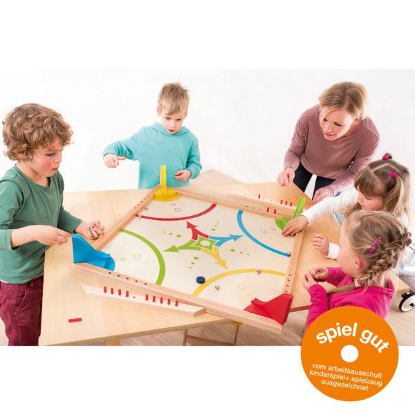 Erwachsene spielt gemeinsam mit Kindern im Kindergarten und Volksschulalter das rasante Kugelspiel Cassado. Außerdem abgebildet ist das Spiel Gut Logo vom Arbeitsausschuß Kinderspiel und Spielzeug mit dem das Brettspiel ausgezeichnet ist