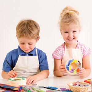 Zwei Kinder im Kindergartenalter gestalten und bemalen den Holzspiegel von beleduc