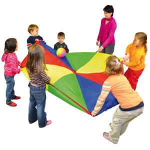 Kinder im Kindergartenalter spielen mit einem Ball auf dem Schwungtuch