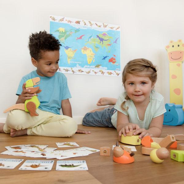2 Kinder im Kinderalter sitzen am Boden und spielen mit dem 64teiligen Dinosaurier-Set Rex & Friends von beleduc