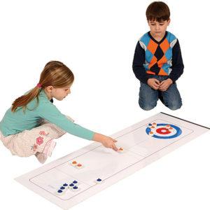 Eine Junge und ein Mädchen im Volksschulalter spielen am Boden mit dem Indoor-Curling-Set