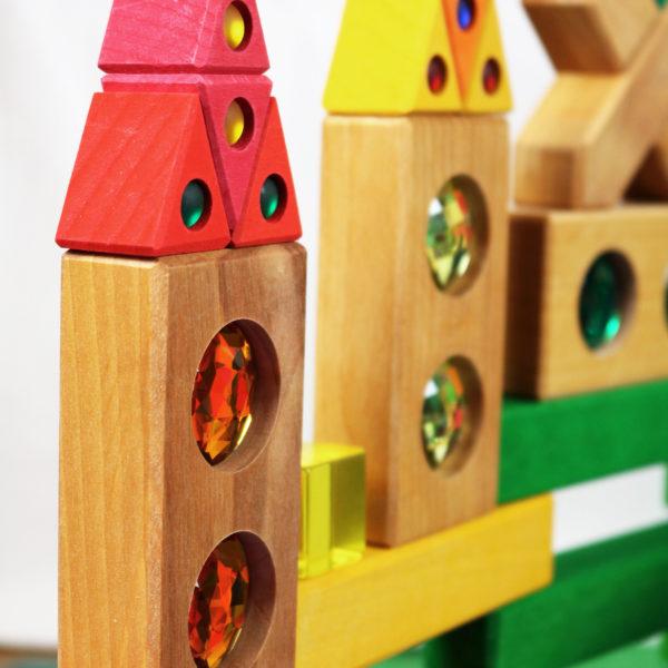 Bauwerk aus Holzbausteinen mit bunten Funkelsteinen aus dem Farbenstraße Baukasten von Bauspiel