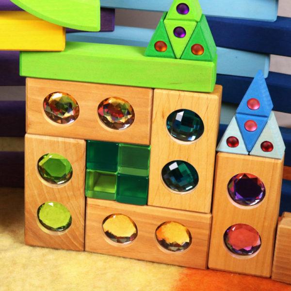 Bauwerk aus Holzbausteinen mit bunten Funkelsteinen aus dem Farbenstraße Baukasten