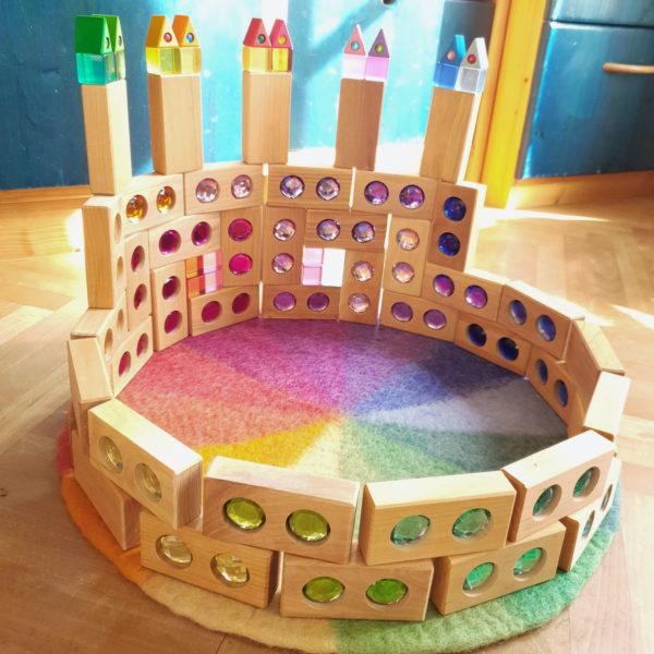 Bauwerk mit den Holzbausteinen der Farbenstraße und dem Farbenkreis aus Filz in Regenbogenfarben