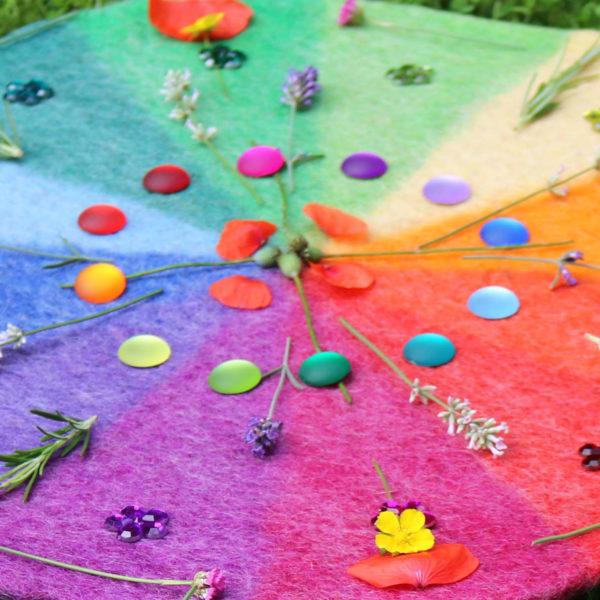 Mandala aus Blumen und matten Funkelsteinen auf dem Farbenkreis aus Filz