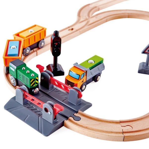 Detailsansicht des Holzeisenbahn-Sets von beleduc für Kinder ab 3 Jahren. Zu sehen die Schienen mti dem Bahnübergang und dem Güterzug