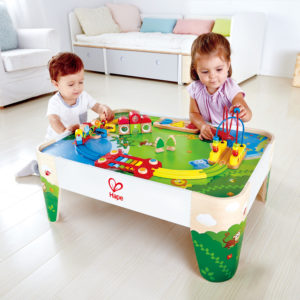 2 Kinder im Krippen- und Kindergartenalter spielen an dem Eisenbahn Spieltisch von beleduc