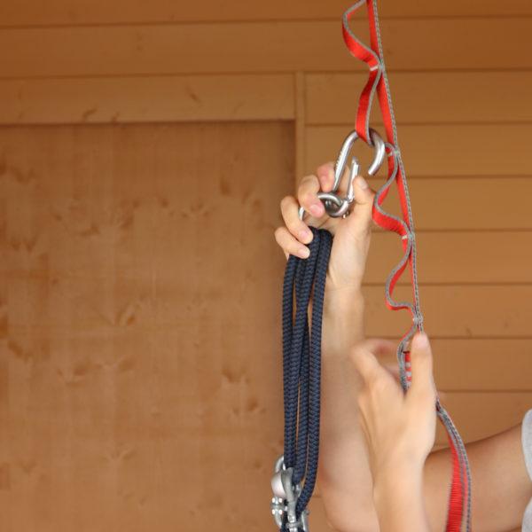 Zu sehen: Hände einer Person, die gerade einen Karabinerhaken in die rote 12-stufige Kletterschlinge einhängt
