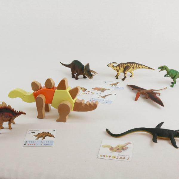 Auszug aus dem Inhalt des großen Dino-Sets von Höller Spiel für Kinder ab 3 Jahren: Holzteile um Dinos zu bauen, Vorlagenkarte mit wichtigen Infos, Saurier-Tierfiguren