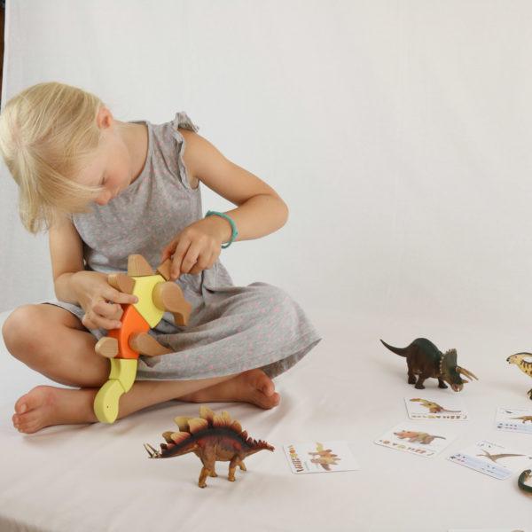 Mädchen im Kindergartenalter spielt mit den zusammensteckbaren Holzteilen des Dino-Sets und baut eine der unendlichen Fantasie-Dino-Varianten