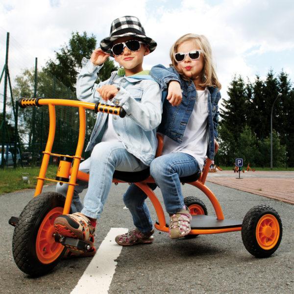 """Zwei Kinder im Kindergartenalter sitzen in cooler Pose mit Sonnenbrille auf dem Dreirad """"Taxi"""" von beleduc in orange"""