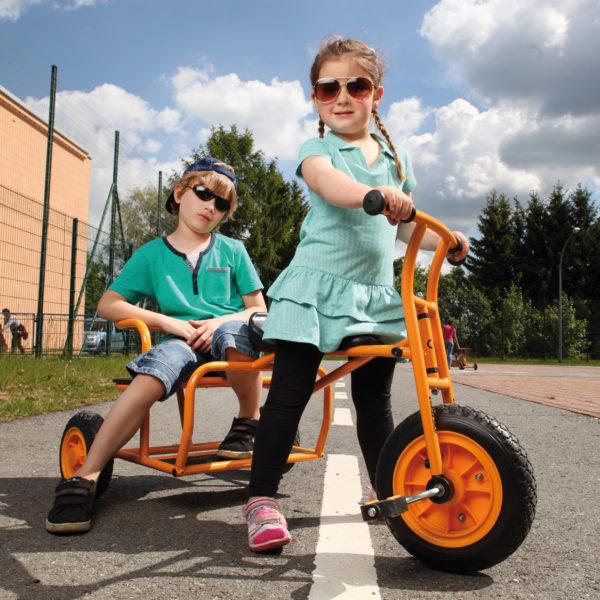 """Zwei Kinder im Kindergartenalter sitzen in cooler Pose mit Sonnenbrille auf dem Dreirad """"Doppeltaxi"""" von beleduc in orange"""