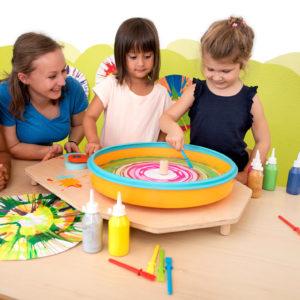 Kinder im Kindergartenalter kreiren mit der Farbschleuder und dem passenden Schaber individulle Kunstewerke