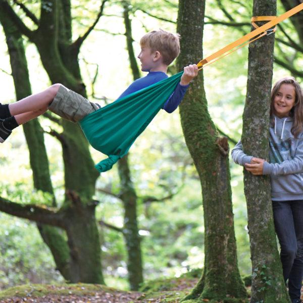 Ein Bub im Schulalter schaukelt in der Taschenschaukel, die im Wald auf einem Baum aufgehängt ist