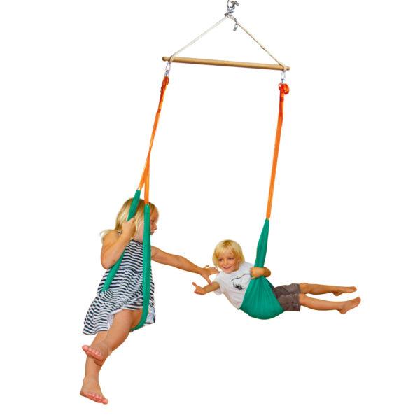 2 Kinder im Kindergartenalter schaukeln gemeinsam in der Flugschaukel bestehend aus einem Trapez als Aufhängung und 2 Taschenschaukeln