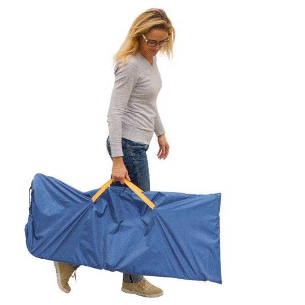 Frau trägt die Klappbank mit einer Hand an den Griffen der Tasche