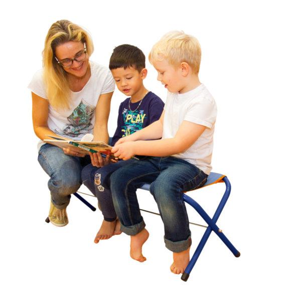 Ein Erwachsener sitzt mit 2 Buben auf der Klappbank und schauen ein Buch an