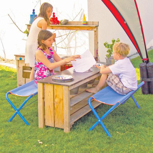 Kinder sitzen auf der Multi Bank im Garten