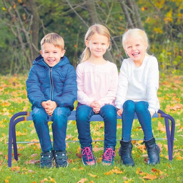 Kinder sitzen auf Mulit Bank im Garten