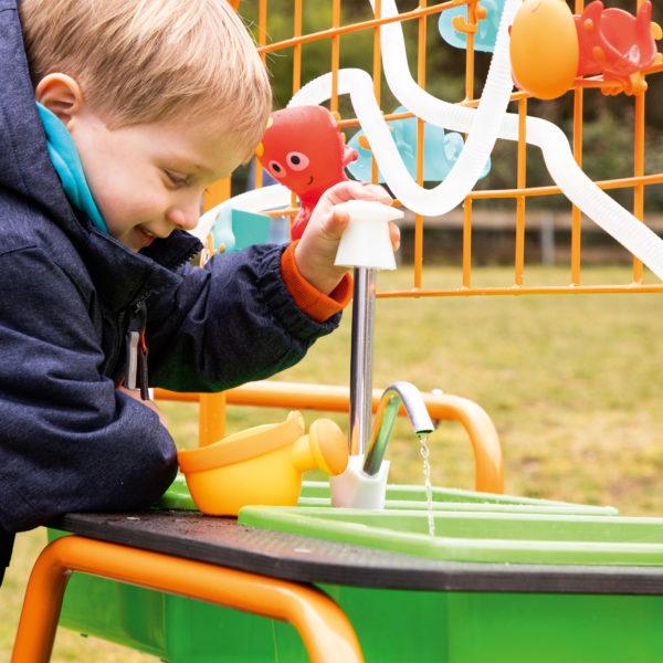 Bub im Kindergartenalter pritschelt vergnügt im Wasserbehälter