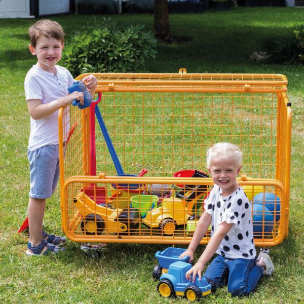 Ein Bub und ein Mädchen im Kindergartenalter vor dem gefüllten Transportwagen von beleduc