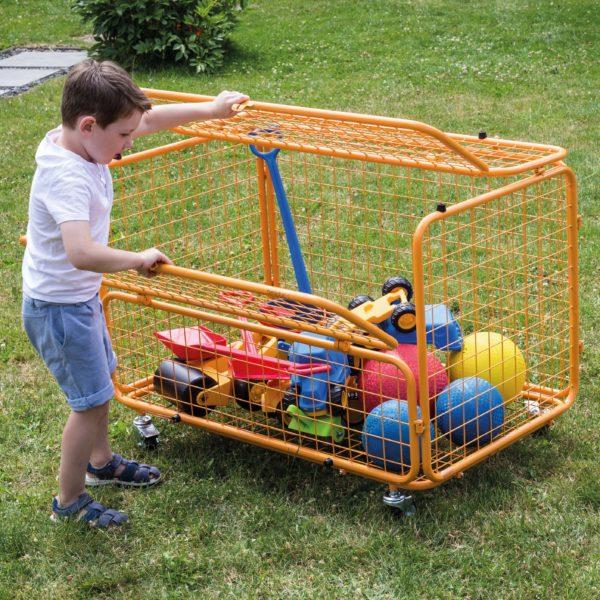 Bub im Kindergartenalter zeigt wie einfach das Öffnen des Transportwagens ist, da sich die Öffnung auf Kinderhöhe befindet