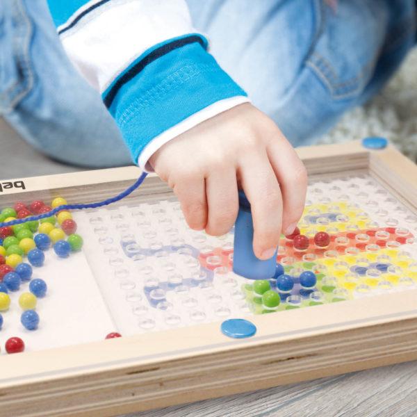 Kinderhand nimmt mit dem Magneten die bunten Kugeln des Lernspiels Logipic auf und legt eine der Motivkarten nach