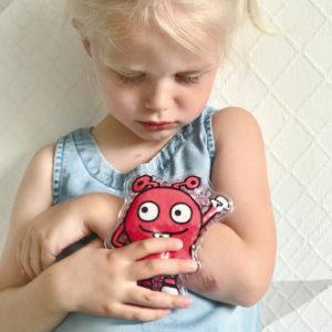 Mädchen im Kindergartenalter hält sich ein rotes Helfermonster als Coolpack auf den verletzten Arm.