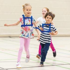 3 Kinder im Kindergartenalter spielen Pferdchen mit der Doppel-Laufleine