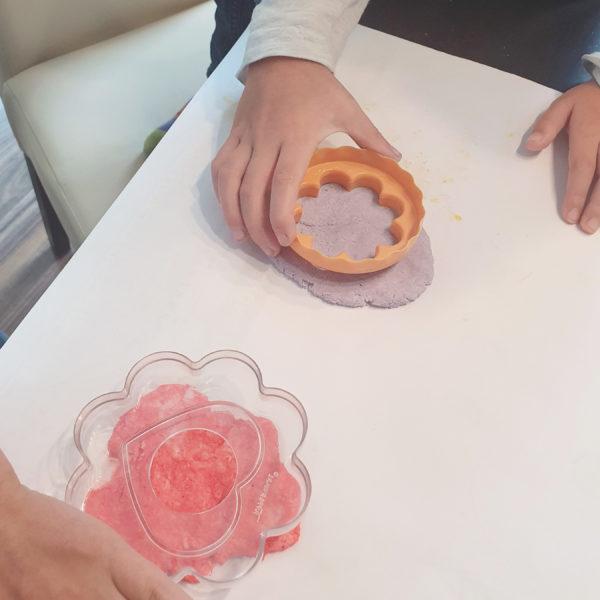 Schritt 4: Kinderhände stechen mit Keksausstechern Motive aus der ausgerollte Seifenmasse