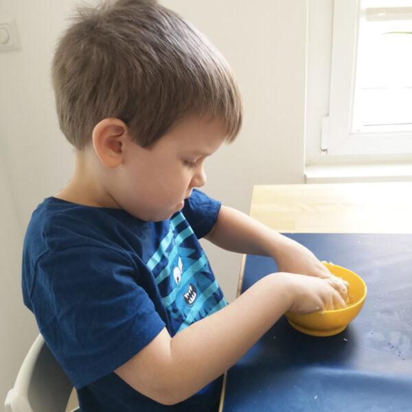 Kind knetet Seifenknete in Schüssel