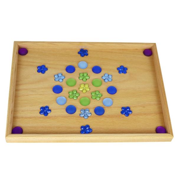 Muster aus Funkelsteinen gelegt auf einem Legetablett aus Holz