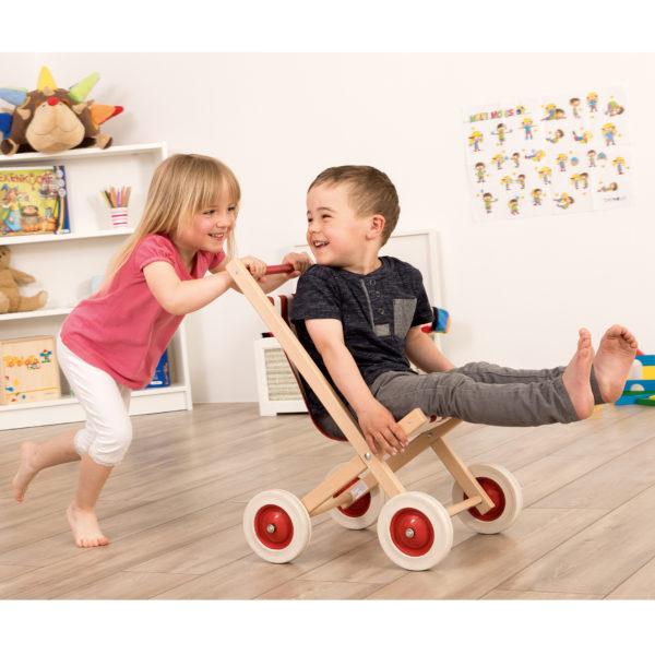 Kinder spielen mit Puppenwagen