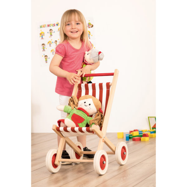 Kind spielt mit Puppenwagen