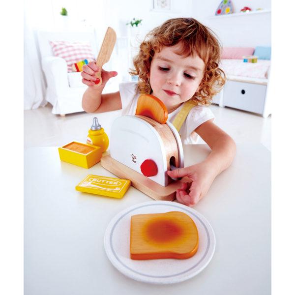 Kind spielt mit Toaster von Hape aus Holz