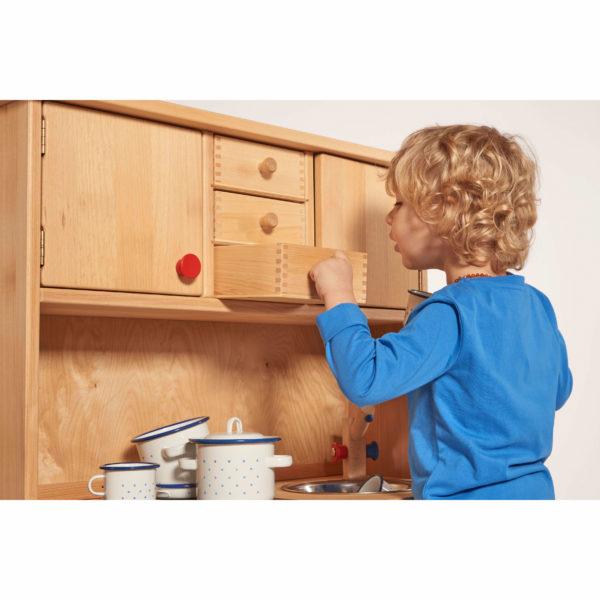 Kind spielt mit Kinderküche aus Holz