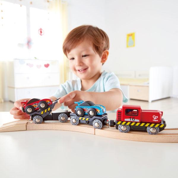 Kind spielt mit Rennwagen Transporter