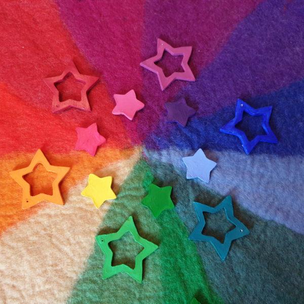 Bunte Sterne aus weißer Modelliermasse bemalt mit Crilix Acrylfarbe in den Farben des Farbenkreises