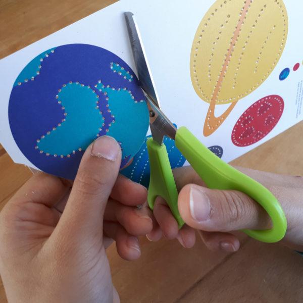 Kind schneidet geprickelten Bastelbogen aus