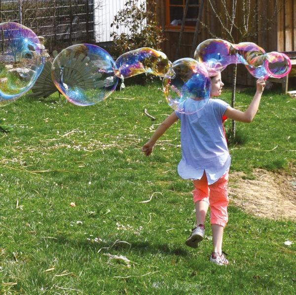 Kind läuft und macht Riesenseifenblasen