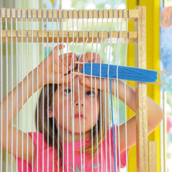Kind webt auf Riesen Webrahmen