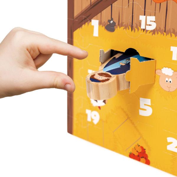 Kind nimmt Holzfigur aus dem Adventskalender