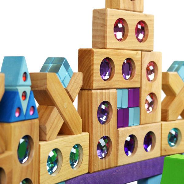 Bauwerk aus Holzbausteinen mit bunten Funkelsteinen in blau und lilatönen aus dem Farbenstraße Baukasten von Bauspiel